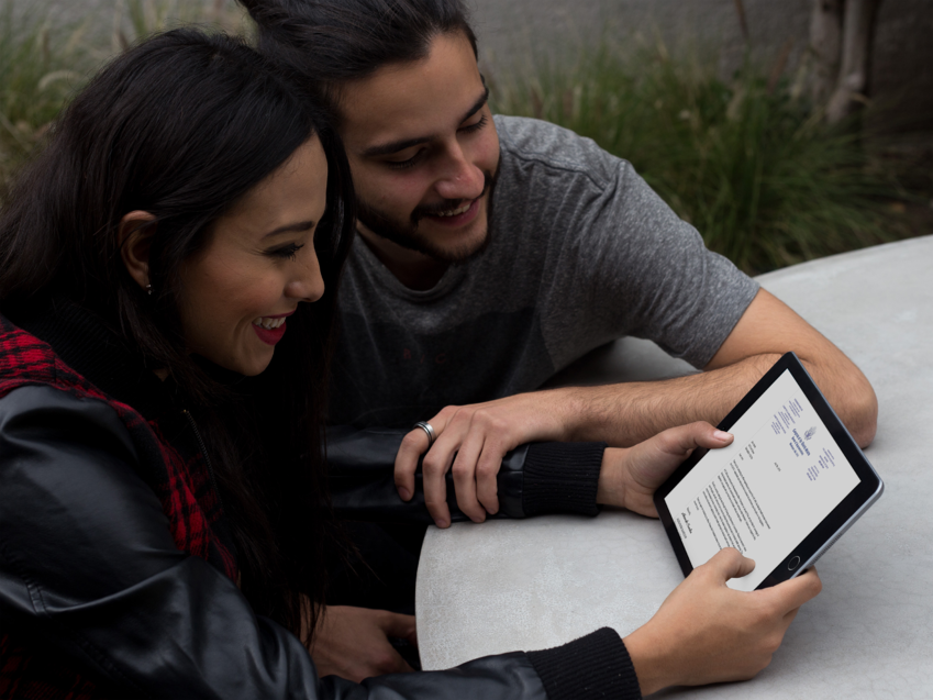 young-couple-using-a-black-ipad-in-landscape-position-at-their-terrace-a13115